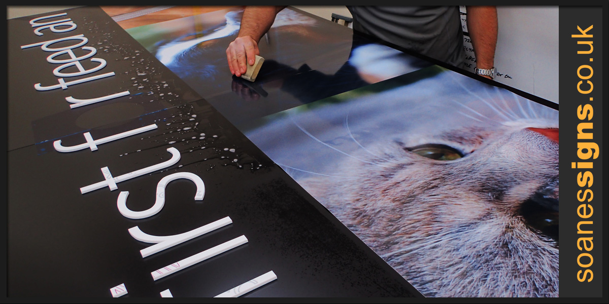 Vinyl graphic print  being wet applied to composite pan shop front sign for Kens Corn Stores