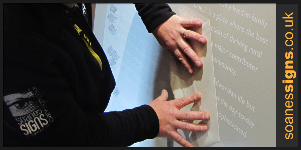 Vinyl text being applied to exhibition wall in Holkham Hall gallery 2015