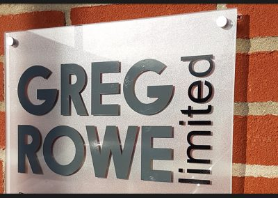 Frosted perspex panel with cut vinyl graphics fitted on metal off-stands for Greg Rowe Ltd