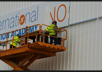 Hangar sign in six sections fabricated from white folded pans with aluminium rail support and vinyl graphics applied, installed for International Aviation Academy Norwich