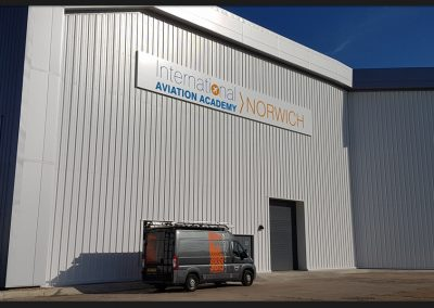 Six sections hangar sign fabricated from white folded pans with aluminium rail support and vinyl graphics applied, installed for International Aviation Academy Norwich