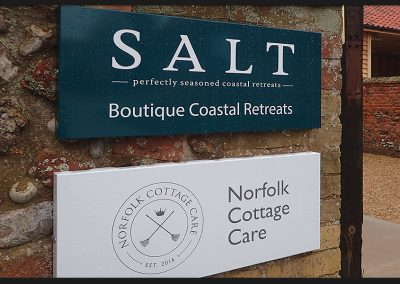 Wall signs from shaped pans with concealed frame and vinyl printed graphics installed for SALT and Norfolk Cottage Care at Holkham Estates