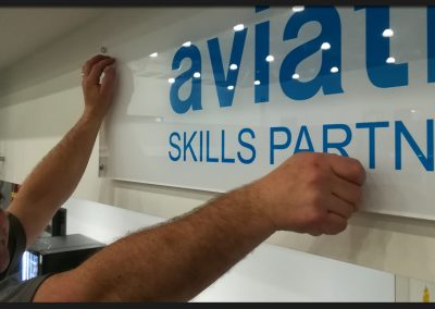 Acrylic signs on metal locators and off-stands reverse decorated with logo branding for sponsors of the International Aviation Academy Norwich