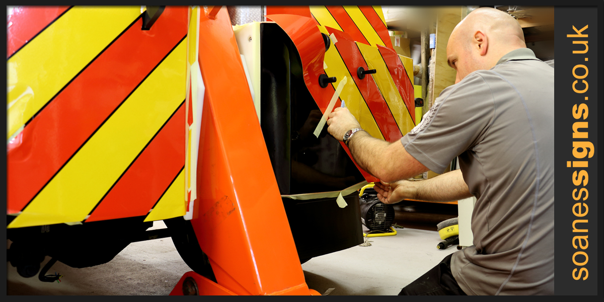 Applying reflective vinyl chevrons to the rear of Delmonte Recovery trucks
